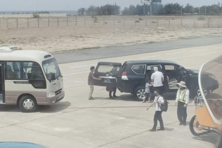 Deputy Secretary Phu Yen drives his car close to the plane to pick up his daughter