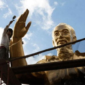 What do critics say about Vietnam continuing to build statues of Ho Chi Minh?